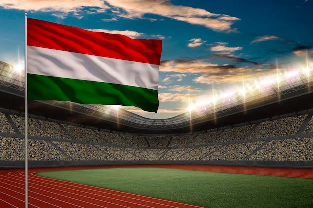 Bandeira húngara em frente a um estádio de atletismo com fãs. Foto gratuita