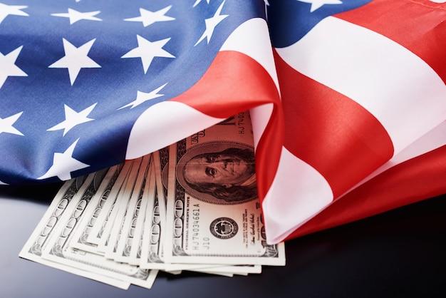 Bandeira nacional dos eua e moeda usd notas de dinheiro em um escuro. negócios e finanças Foto Premium