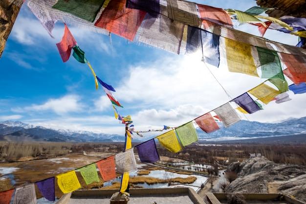Bandeiras budistas coloridas da oração no marco bonito de leh ladakh da montanha de leh em india. Foto Premium