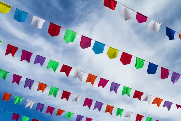 Bandeiras coloridas bonitos pequenas na corda que pendura fora para o feriado com o fundo branco brilhante das nuvens do céu azul. itália, sardenha. Foto gratuita