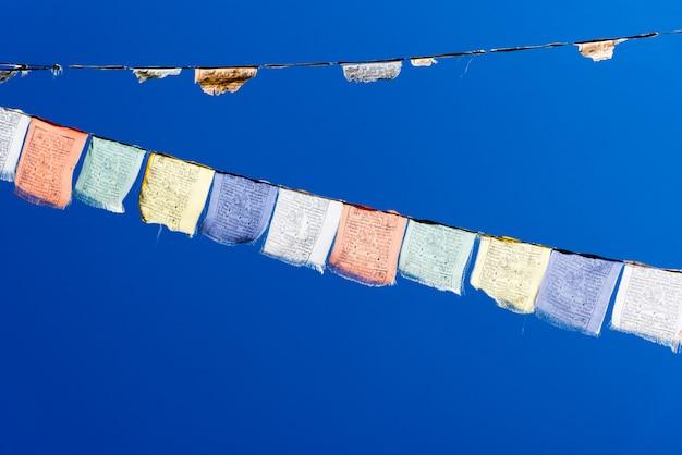 Bandeiras de oração coloridas sobre o céu azul. Foto Premium