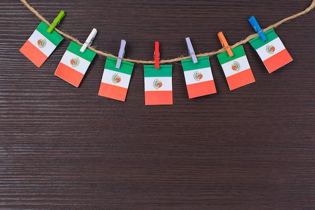 Bandeiras do méxico no varal anexado com prendedores de roupa de madeira Foto Premium