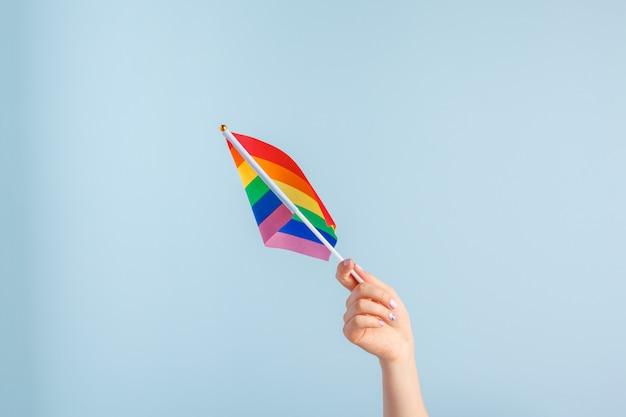 Bandeiras gays na mão das mulheres em fundo cinza Foto Premium