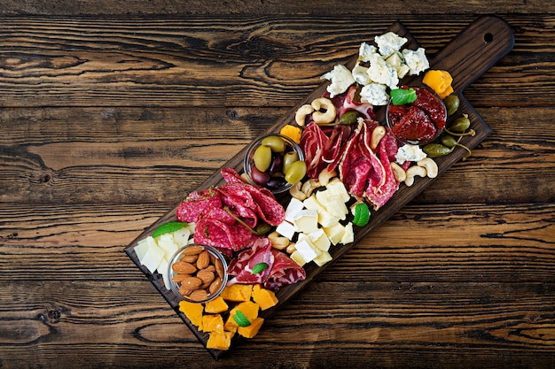 Bandeja antepasto da restauração com bacon, carne seca, salsicha, queijo azul e uvas em uma tabela de madeira. vista do topo Foto gratuita