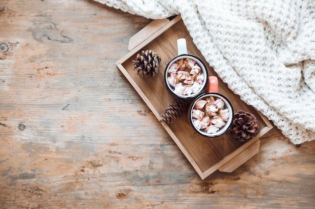 Bandeja com chocolate quente perto de cobertor Foto gratuita