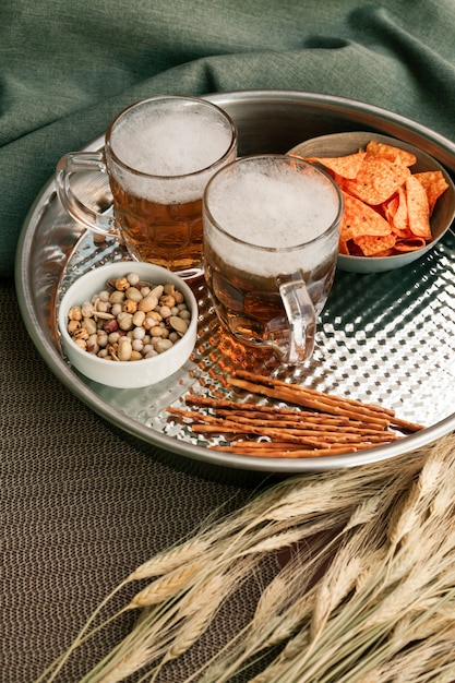 Bandeja com copos de cerveja e lanches Foto gratuita