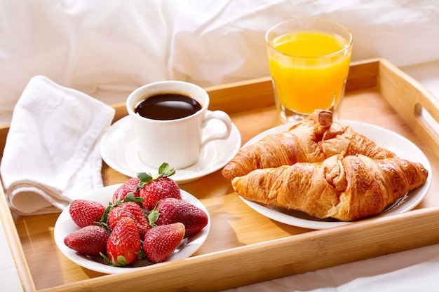 Bandeja de café da manhã na cama: café, croissants, suco e morangos frescos Foto Premium