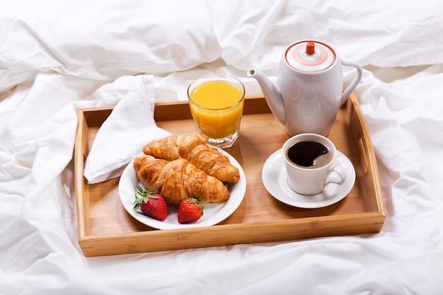 Bandeja de café da manhã na cama, suco de croissants com café e morangos frescos Foto Premium