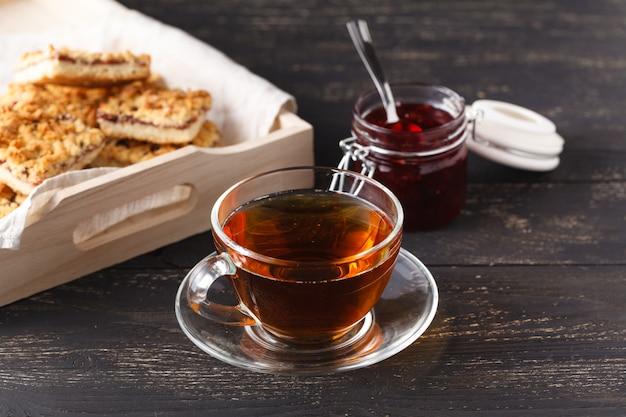 Bandeja de madeira com uma xícara de chá e biscoitos Foto Premium