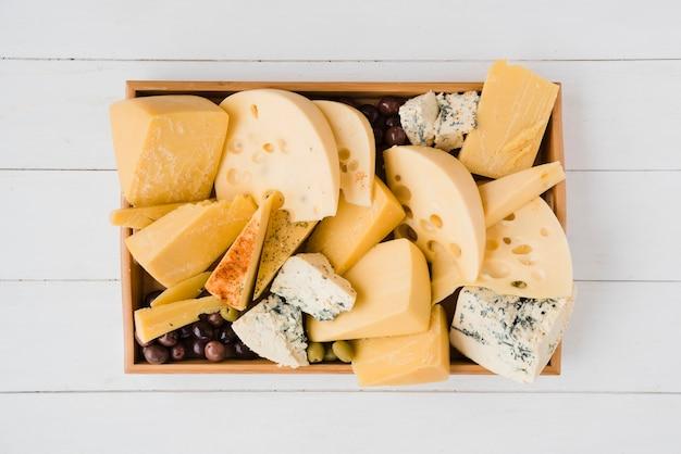 Bandeja de madeira com várias fatias do queijo suíço médio-duro com azeitonas verdes Foto gratuita