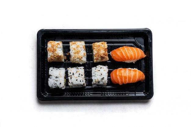 Bandeja de sushi com california roll e maki em uma bandeja de reciclagem preta, localizada em uma mesa de madeira. prato gastronômico japonês em reciclável. Foto Premium