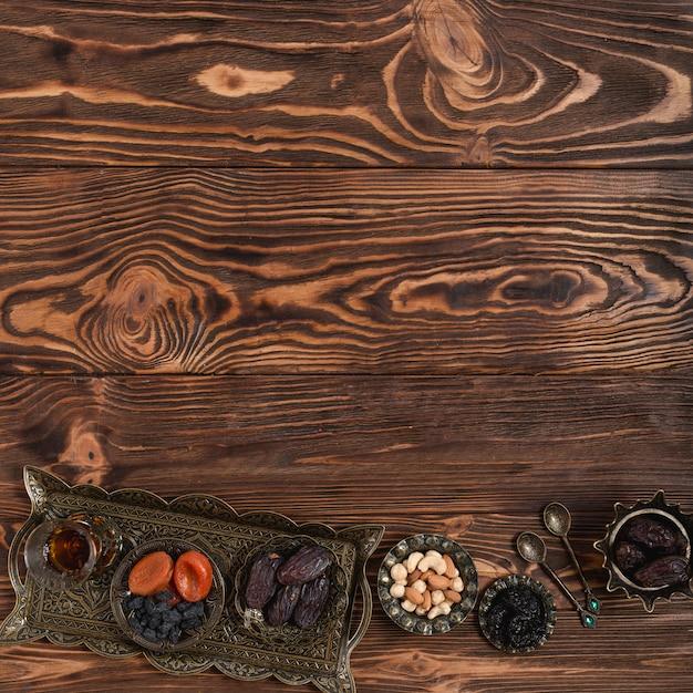 Bandeja metálica turca tradicional com vidro de chá; frutas secas e nozes no pano de fundo texturizado de madeira com espaço para escrever o texto Foto gratuita