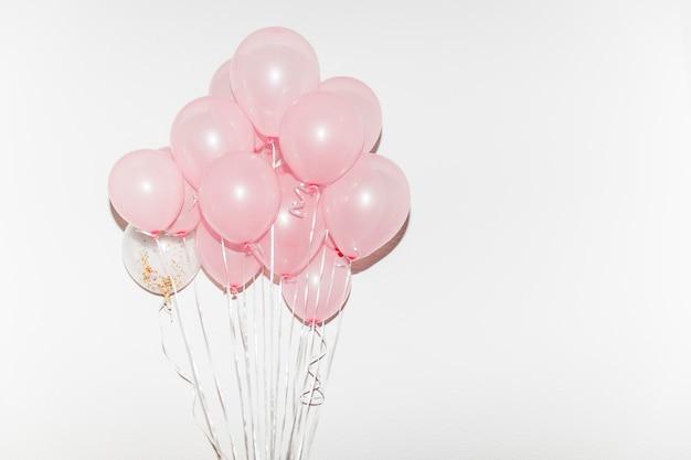 Bando de balões rosa isolado no fundo branco Foto gratuita
