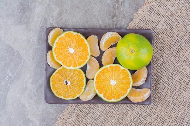 Bando de fatias de tangerina e segmentos na placa preta. Foto gratuita