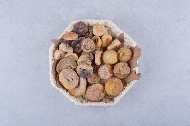 Bando de figos secos doces colocados em uma cesta de vime. Foto gratuita