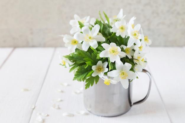 Bando de flores de primavera branca em caneca de ferro Foto Premium
