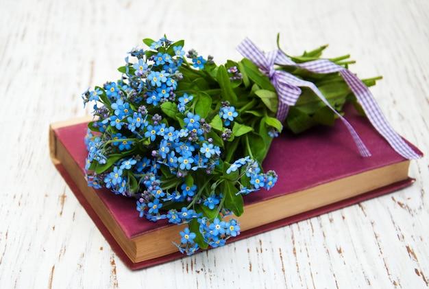 Bando de flores miosótis e livro antigo Foto Premium