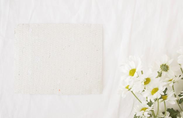 Bando de lindas flores em caules verdes perto de papel reciclado Foto gratuita