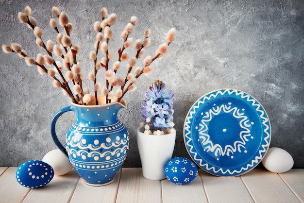 Bando de salgueiro em jarro de cerâmica azul com placa a condizer, ovos de páscoa e decoração de primavera Foto Premium