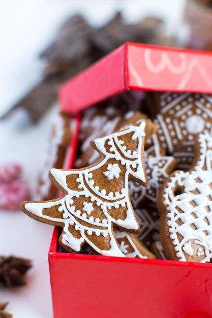 Bando de tradicional natal gingerbread com cobertura em uma caixa de papel vermelho Foto gratuita