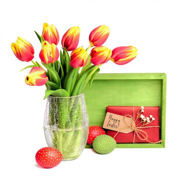 Bando de tulipas vermelhas, placa de madeira, presente com tag e ovos de páscoa coloridos em branco Foto Premium