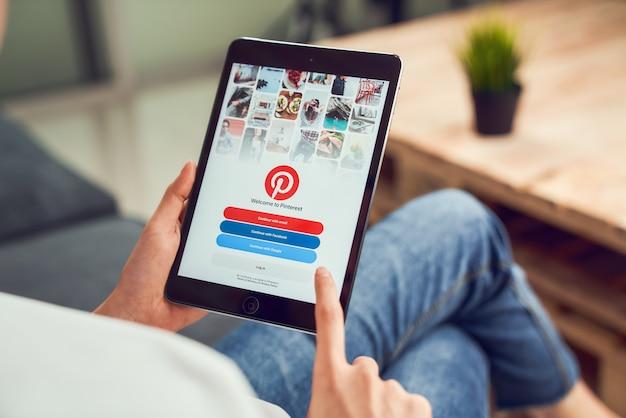 Bangkok, tailândia - 15 de janeiro de 2020: mão de uma mulher segurando o tablet e exibir o serviço de internet social pinterest na tela. é um quadro de anúncios on-line que permite que as pessoas fixem suas coisas interessantes. Foto Premium