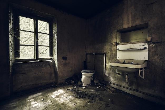 Banheiro com pia na parede coberto de sujeira sob as luzes em um prédio abandonado Foto gratuita