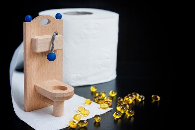 Banheiro de brinquedo de madeira, cápsulas e papel em preto Foto Premium