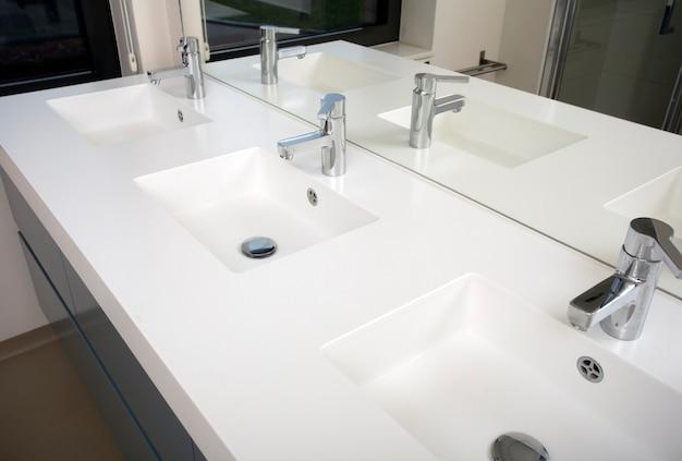 Banheiro de três lavatórios com três lavatórios e três torneiras com design moderno branco com espelho Foto Premium