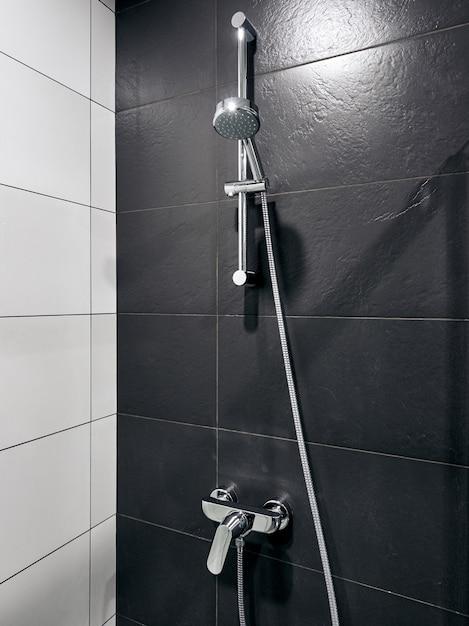 Banheiro e chuveiro no hotel com paredes cinza e brancas Foto Premium