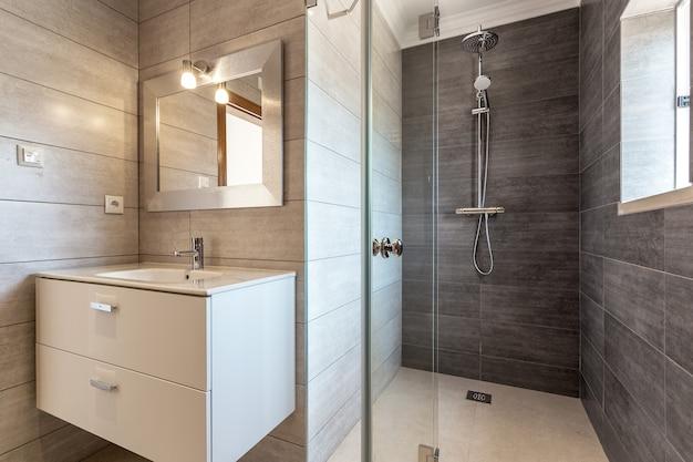 Banheiro moderno com chuveiro e pia para higiene. Foto Premium