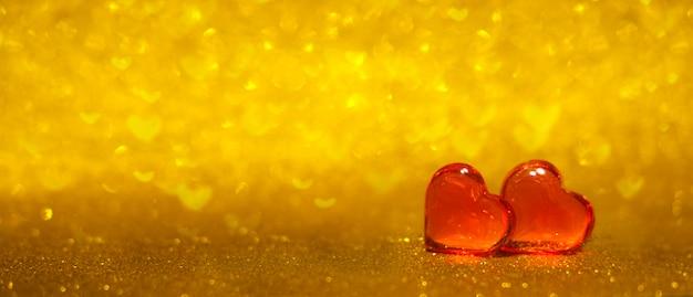 Banner com dois corações vermelhos em fundo brilhante ouro bokeh. copyspace. Foto Premium