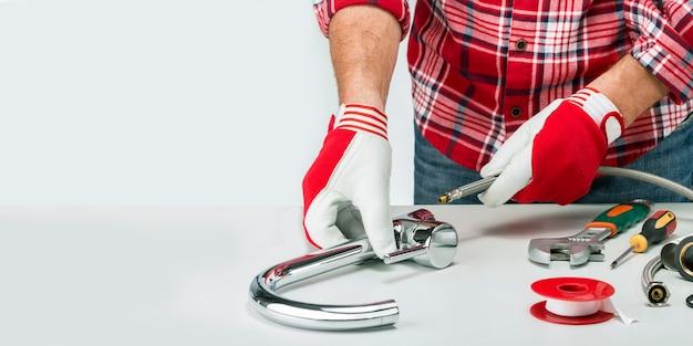 Banner de encanador profissional com encanador e ferramentas, encaixe e torneira de água. instalação fauset com espaço de cópia. Foto Premium