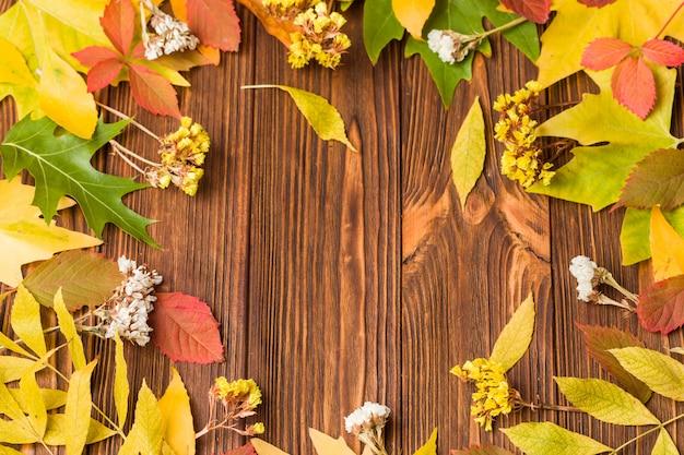 Banner de outono com folhas de árvore colorida e flores secas em madeira marrom Foto Premium