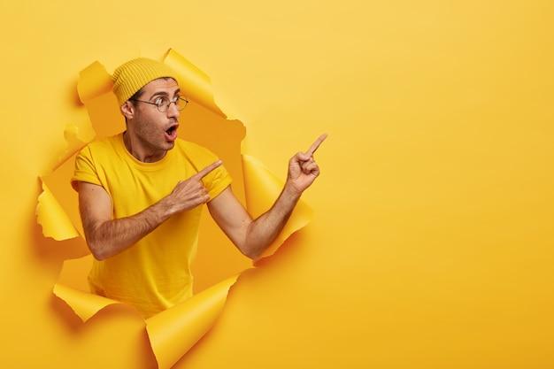 Banner de publicidade com espaço de cópia. emocionalmente surpreso e elegante usando um chapéu amarelo Foto gratuita
