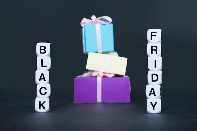 Banner de venda com a palavra texto sexta-feira negra e caixas de presente multicoloridas. Foto Premium
