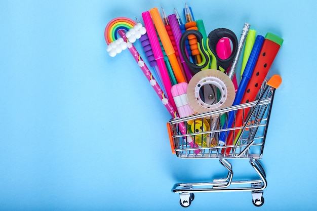 Banner do carrinho de compras com material escolar sobre um fundo azul com espaço de cópia, volta às aulas Foto Premium