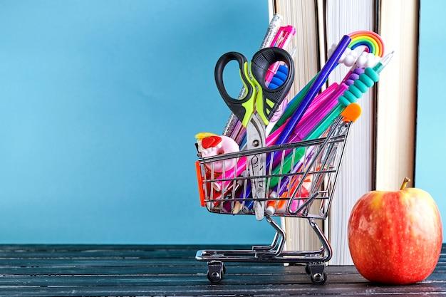 Banner do carrinho de compras com material escolar Foto Premium
