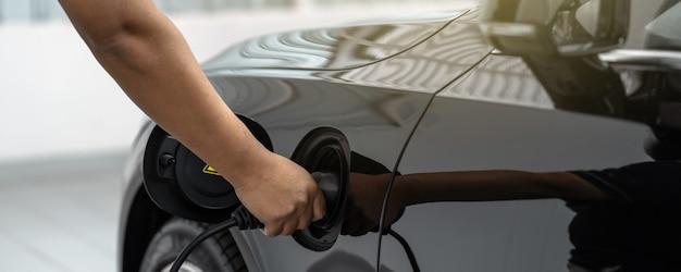 Banner do closeup asiático técnico mão está carregando o carro elétrico ou ev no centro de serviço Foto Premium