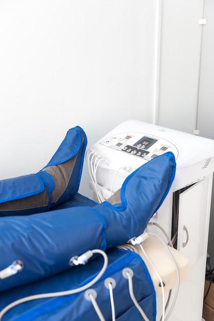 Banner vertical com espaço de cópia com as pernas da mulher em uma capa especial no salão de beleza. tratamento corporal alternativo. massagem anti-gordura pressoterapia. Foto Premium
