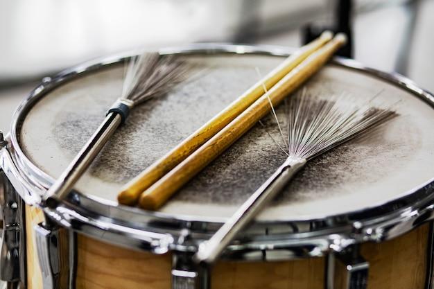 Baquetas e escovas de arame em um velho tambor de couro Foto Premium
