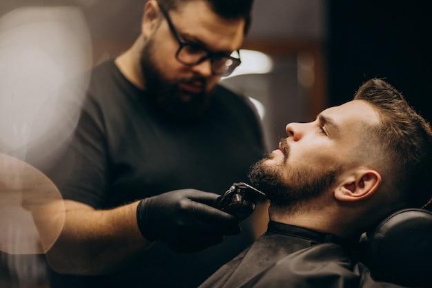 Barba de corte de homem bonito em um salão de barbearia Foto gratuita
