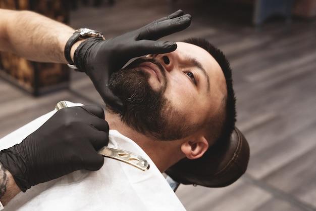 Barbear uma barba em uma barbearia com uma navalha perigosa. Foto Premium