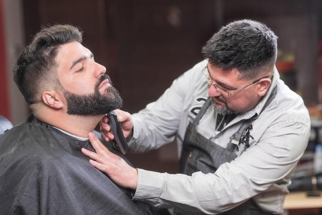 Barbeiro barbeando a barba de um homem barbudo bonito com um barbeador elétrico na barbearia. Foto Premium