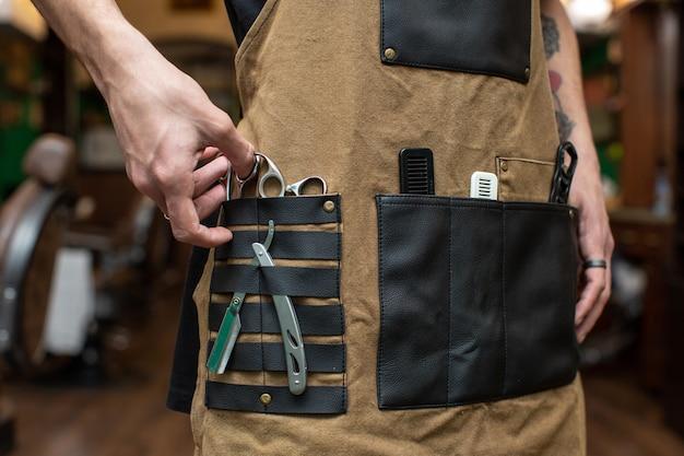 Barbeiro com várias ferramentas nos bolsos Foto gratuita