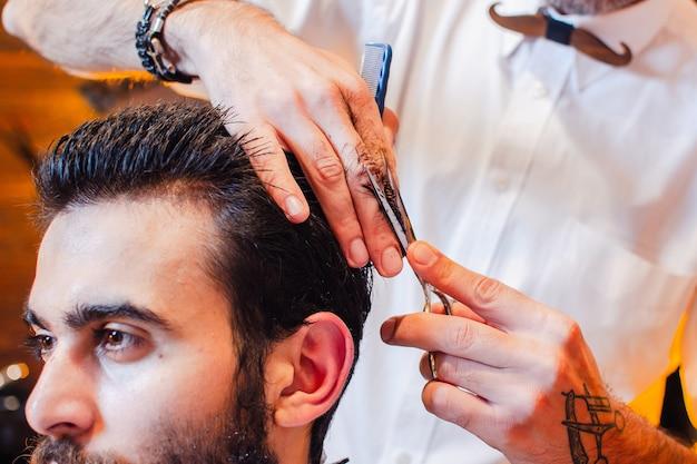 Barbeiro corta o cabelo na cabeça Foto Premium