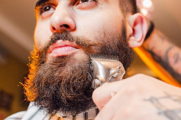 Barbeiro corta uma barba de tosquiadores de cabelo vintage Foto Premium