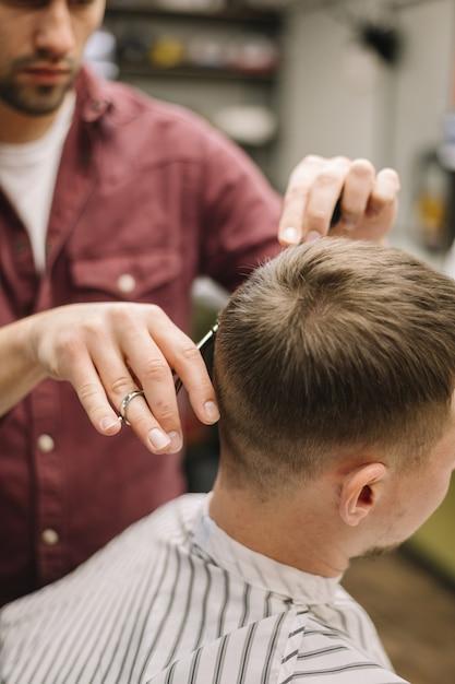 Barbeiro dando um corte de cabelo a um cliente Foto gratuita