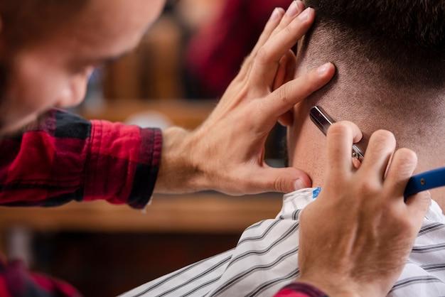 Barbeiro de close-up, terminando um corte de cabelo Foto gratuita