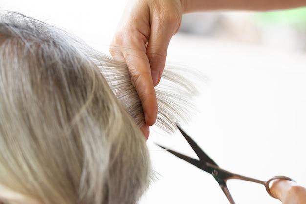 Barbeiro de closeup com cabelo de corte de tesoura Foto Premium